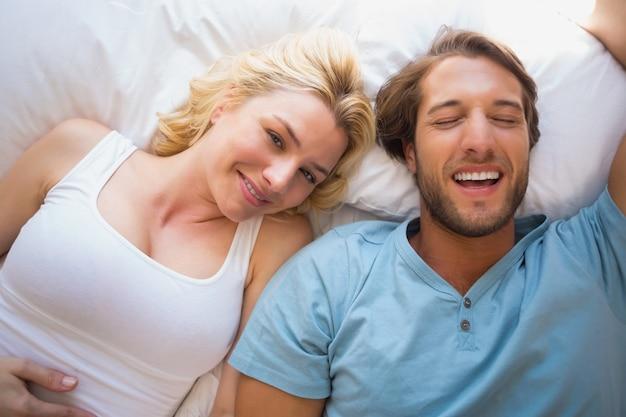 Coppia felice rilassante sul letto