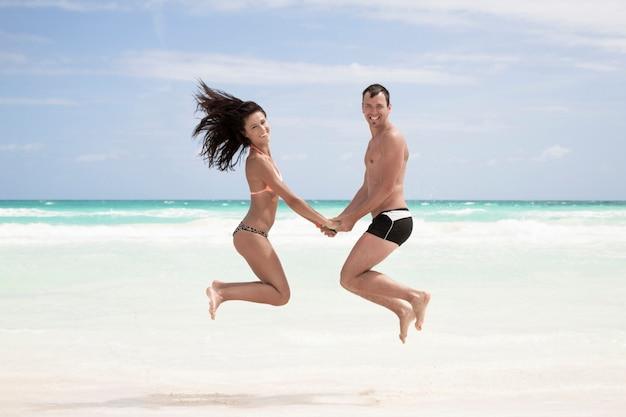 Coppia felice saltando sulla spiaggia
