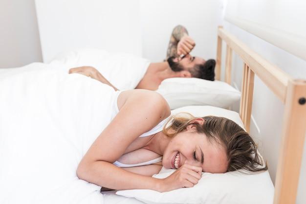 Coppia felice sdraiata sul letto