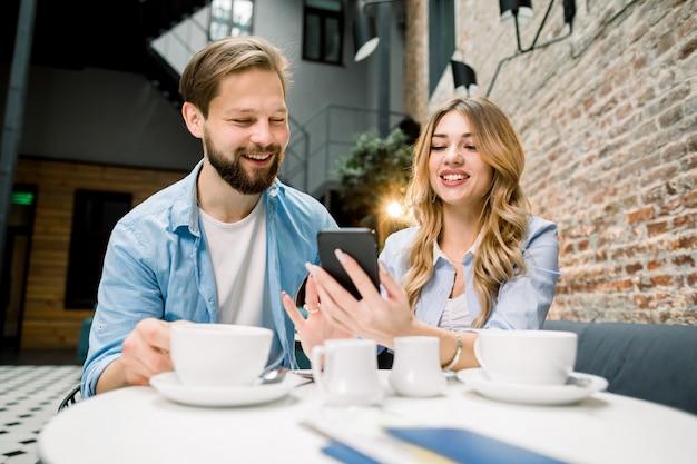 Coppia felice seduto al tavolo, bere caffè o tè, guardare i social media su un telefono in un ristorante, bar o hotel.