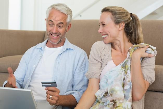 Coppia felice shopping online sul divano