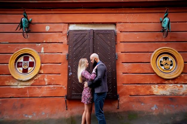 Coppia felice sorridente, in piedi vicino al muro tra le braccia