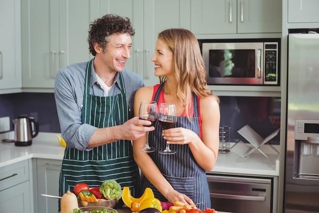 Coppia felice tintinnio con un bicchiere di vino
