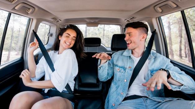 Coppia felice vista frontale ballare all'interno dell'auto