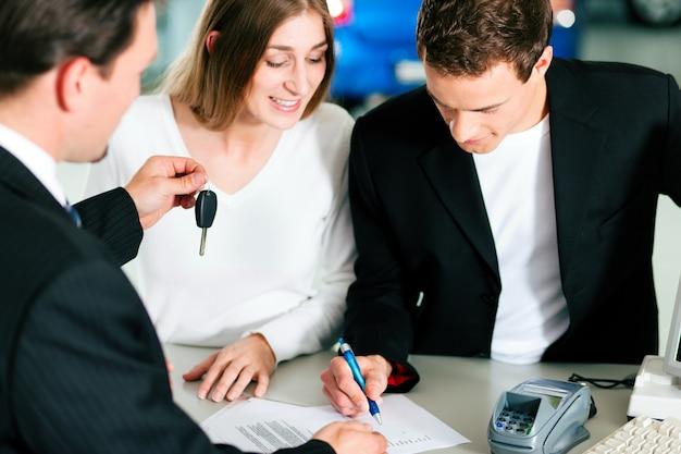Coppia firma il contratto di vendita al rivenditore di auto