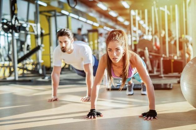 Coppia forte in forma sportiva facendo squat in palestra. obiettivi di coppia.