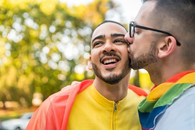 Coppia gay abbracciando e mostrando il loro amore con la bandiera arcobaleno.