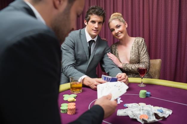 Coppia giocando a poker e sorridente
