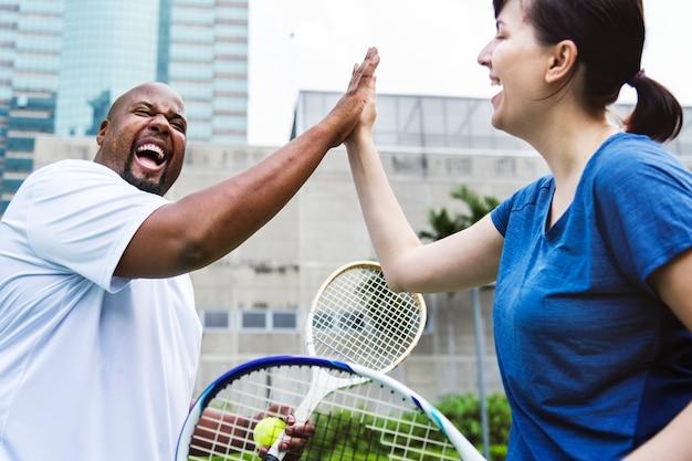 Coppia giocando a tennis in gruppo
