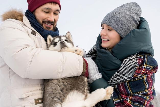 Coppia giocando con husky puppy