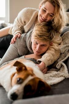 Coppia giocando con il cane nel letto
