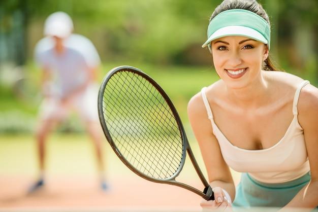 Coppia giocando in doppio al campo da tennis.