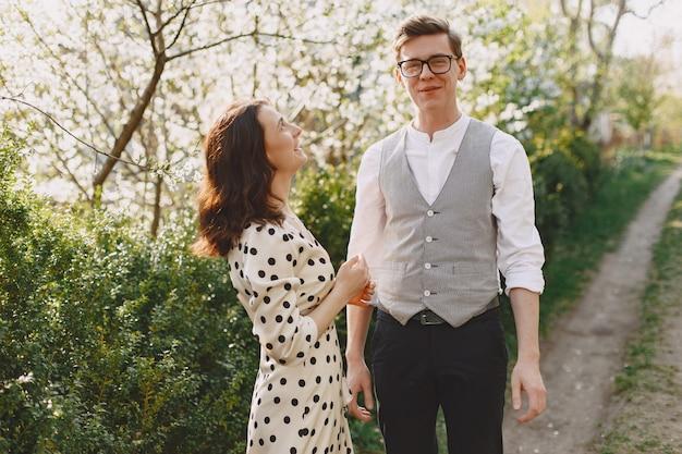 Coppia giovane e donna in un giardino fiorito