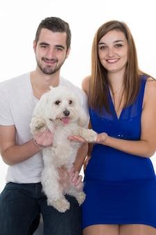 Coppia giovane e felice con il loro amorevole cane bianco