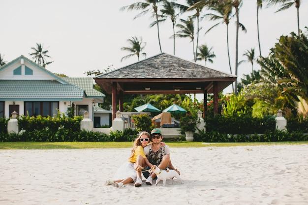 Coppia giovane elegante hipster in amore camminare e giocare con il cane in spiaggia tropicale