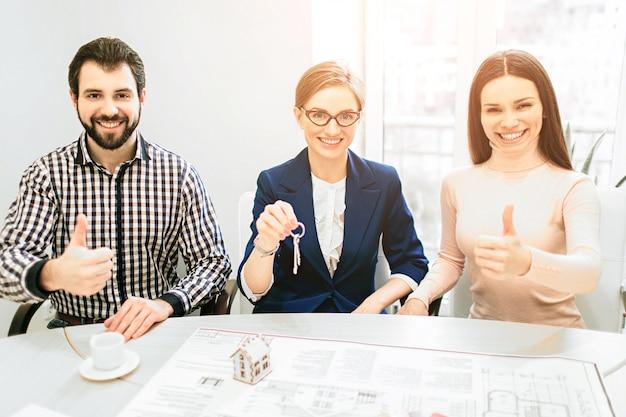 Coppia giovane famiglia acquisto affitto proprietà immobiliare. agente che consulta l'uomo e la donna. firma del contratto per l'acquisto di casa o appartamento o appartamenti