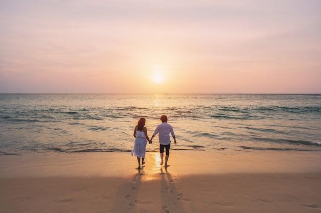 Coppia giovane guardando il bellissimo tramonto sulla spiaggia