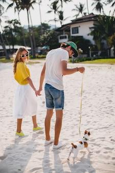 Coppia giovane hipster alla moda hipster in amore camminare e giocare con il cane in spiaggia tropicale