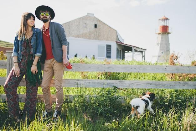 Coppia giovane hipster alla moda innamorata che cammina con il cane in campagna, moda boho stile estivo
