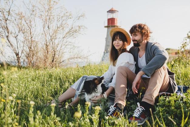 Coppia giovane hipster alla moda innamorata del cane in campagna, seduto sull'erba