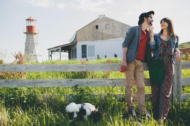 Coppia giovane hipster alla moda nell'amore che cammina con il cane in campagna