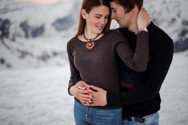 Coppia giovane, in jeans e maglioni lavorati a maglia, abbracciati sulla scena delle montagne di neve