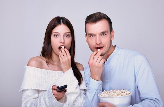 Coppia giovane in piedi insieme, guardare film, mangiare popcorn.