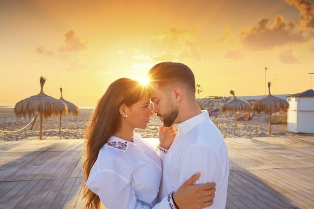 Coppia giovane innamorato abbraccio sulla spiaggia
