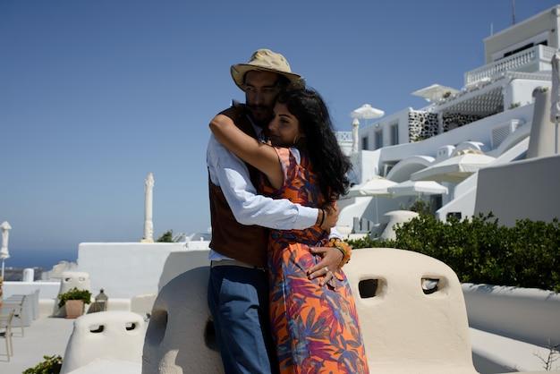 Coppia giovane luna di miele sull'isola più romantica di santorini, in grecia. tramonto nella città di oia