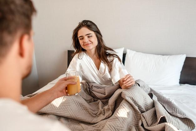 Coppia giovane nel letto. la bella donna sorridente sta bevendo il succo di mattina, fuoco selettivo