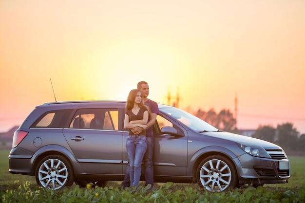 Coppia giovane, sottile attraente donna dai capelli lunghi e uomo bello abbracciati insieme appoggiandosi alla macchina d'argento nel campo verde nella campagna rurale sul cielo luminoso al tramonto