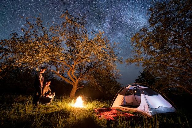 Coppia giovane turisti in piedi a un falò vicino alla tenda sotto gli alberi e il bel cielo notturno pieno di stelle e via lattea. notte in campeggio