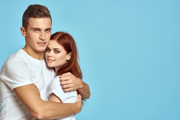 Coppia giovane uomo e donna in magliette bianche su sfondo azzurro