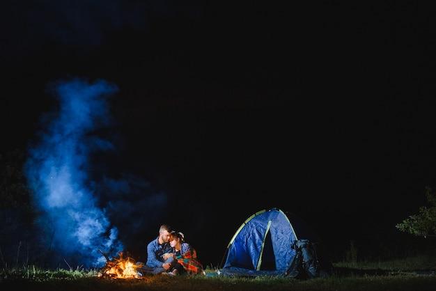 Coppia giovane uomo e donna trevelers seduto vicino a incandescente tenda turistica, fuoco ardente, sulla cima della montagna