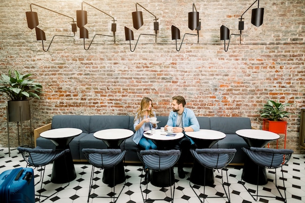 Coppia godendo il tempo del caffè seduti al tavolo in hotel, in attesa del check-in per l'arrivo.