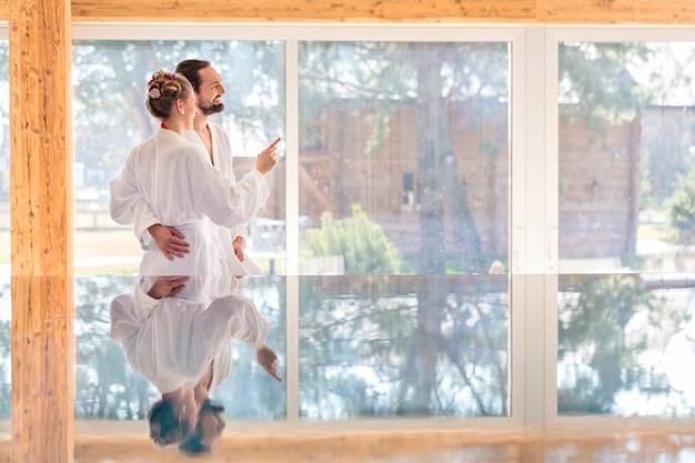 Coppia godendo la vista sulla piscina termale benessere