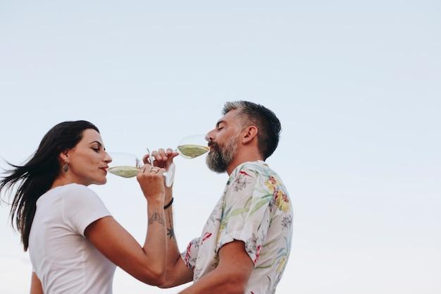 Coppia godendo un bicchiere di vino sulla spiaggia