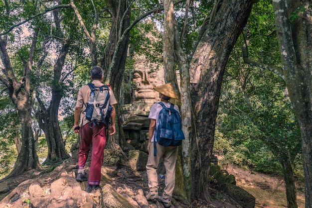 Coppia guardando facce di pietra nella giungla