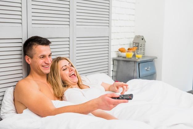 Coppia guardando la tv a letto