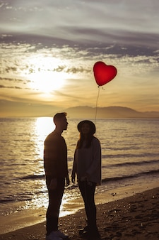 Coppia guardando palloncino cuore volante sulla riva del mare in serata