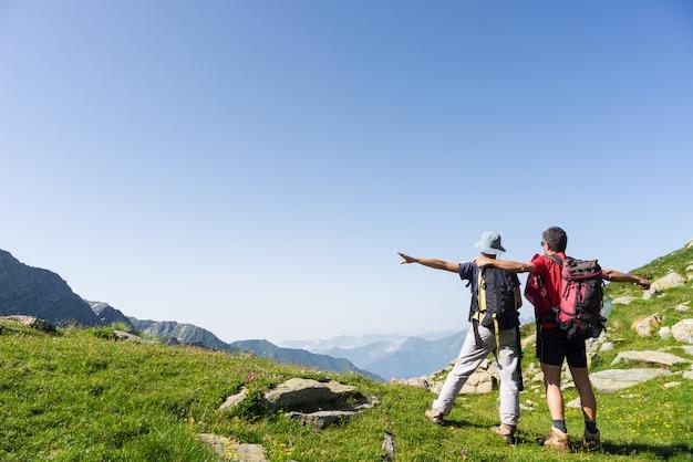 Coppia guardando panorama in alto nelle alpi