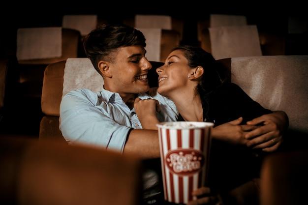 Coppia guardare film in teatro con popcorn sorriso e faccia felice