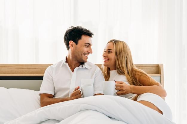 Coppia il caffè bevente felice sorridente dell'amante caucasico insieme nel primo mattino della camera da letto