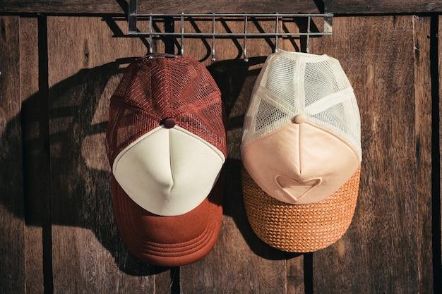 Coppia il cappello dell'uomo e delle donne che appendono sulla parete di legno