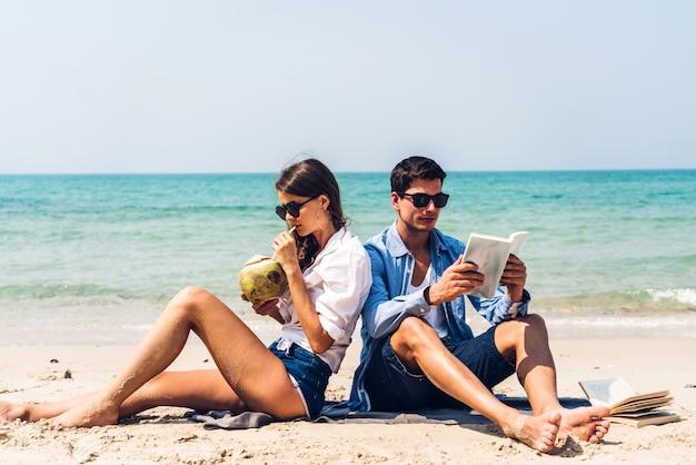 Coppia il succo e il libro di lettura beventi della noce di cocco sulla spiaggia