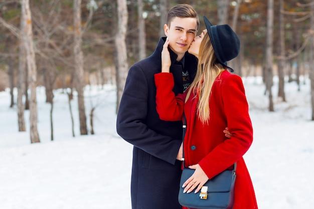 Coppia in abiti invernali in posa in una giornata nevosa
