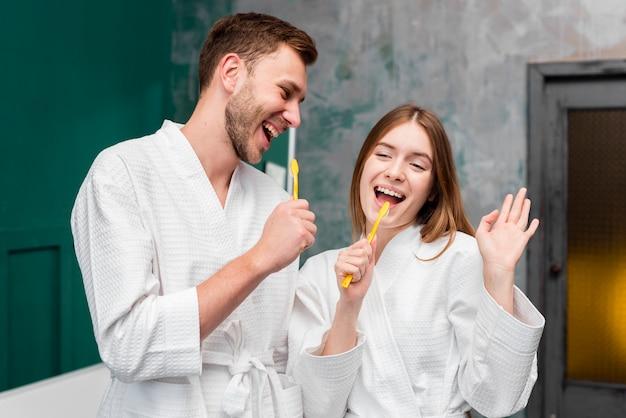 Coppia in accappatoi a scherzare con spazzolini da denti