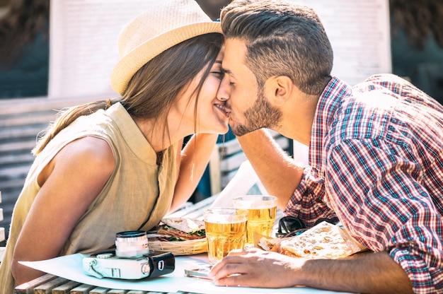 Coppia in amore baci al bar a mangiare cibo locale in escursione di viaggio