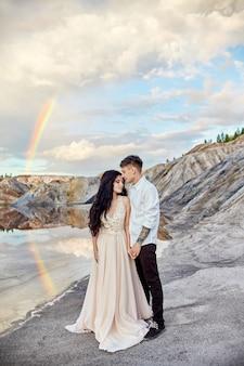 Coppia in amore baci e abbracci con arcobaleno e montagne