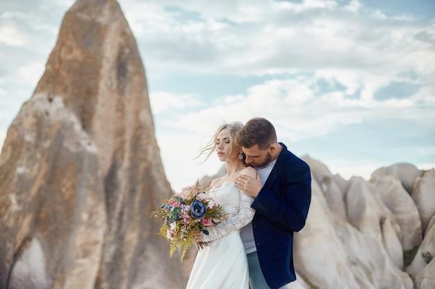 Coppia in amore baci e abbracci in favolose montagne in natura.